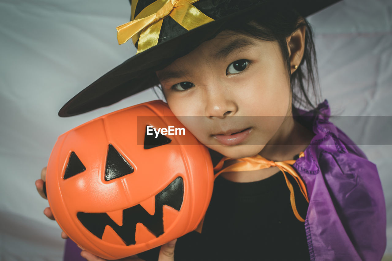 halloween, childhood, child, pumpkin, celebration, orange color, one person, jack o' lantern, real people, portrait, lifestyles, focus on foreground, front view, smiling, holiday - event, males, girls, anthropomorphic face, innocence