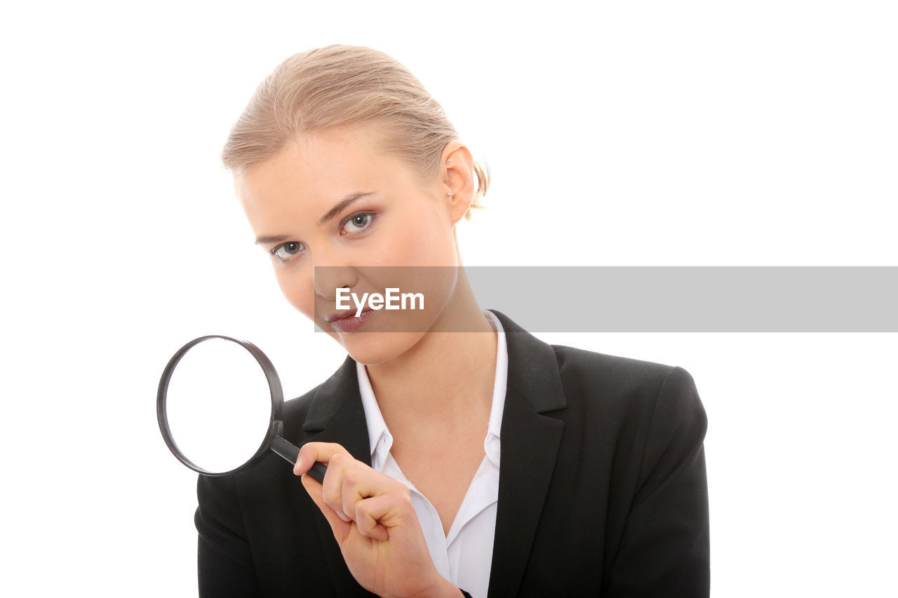 Close-up of businesswoman with magnifying glass against white background