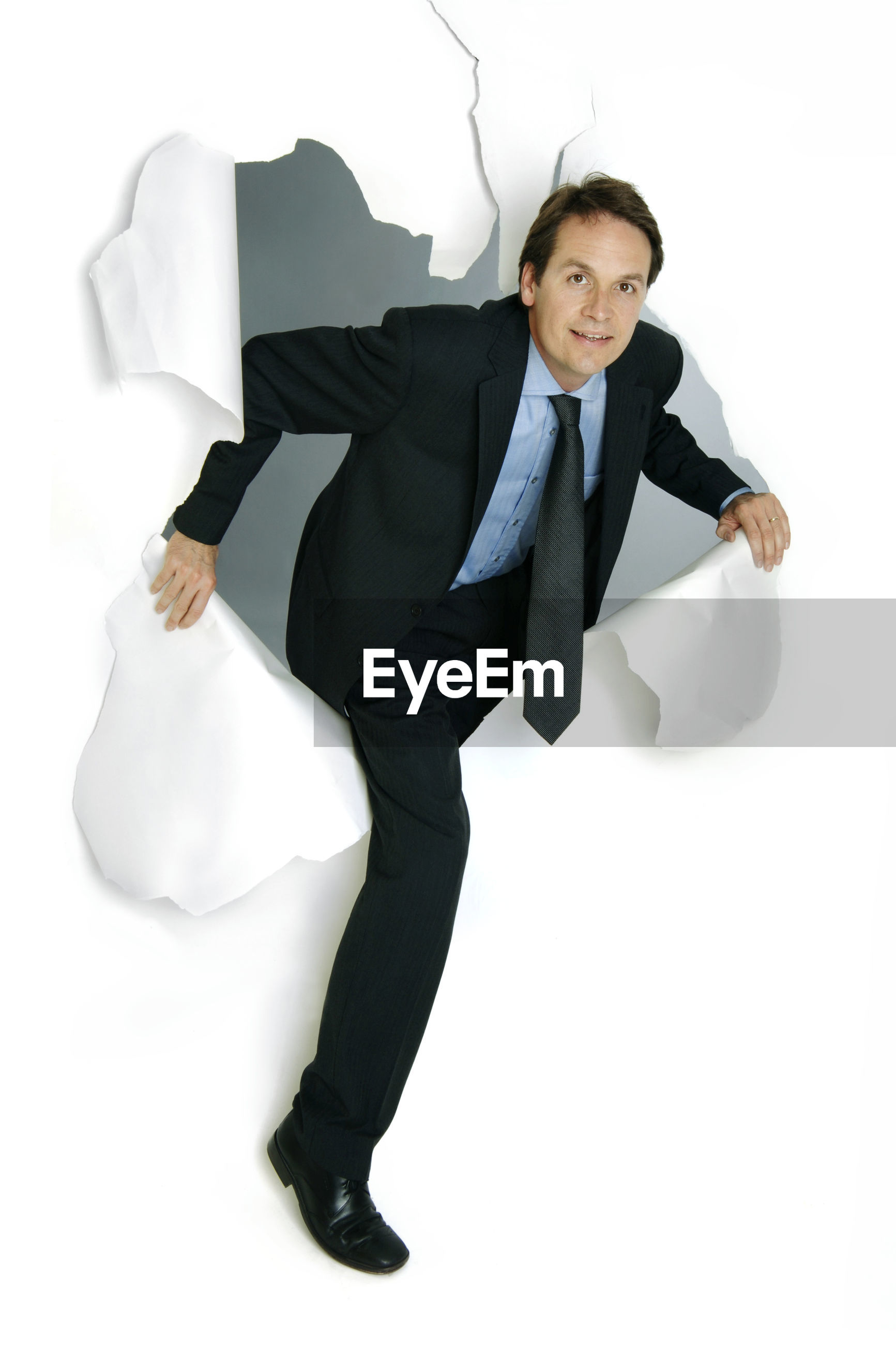 Portrait of businessman with torn paper over white background