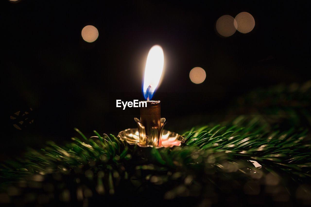 Close-Up Of Illuminated Candle At Night