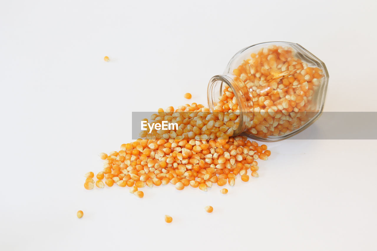 food, food and drink, studio shot, indoors, white background, still life, wellbeing, freshness, healthy eating, no people, orange color, close-up, copy space, cut out, vegetable, bean, corn, lentil, spilling, sweetcorn, temptation, snack