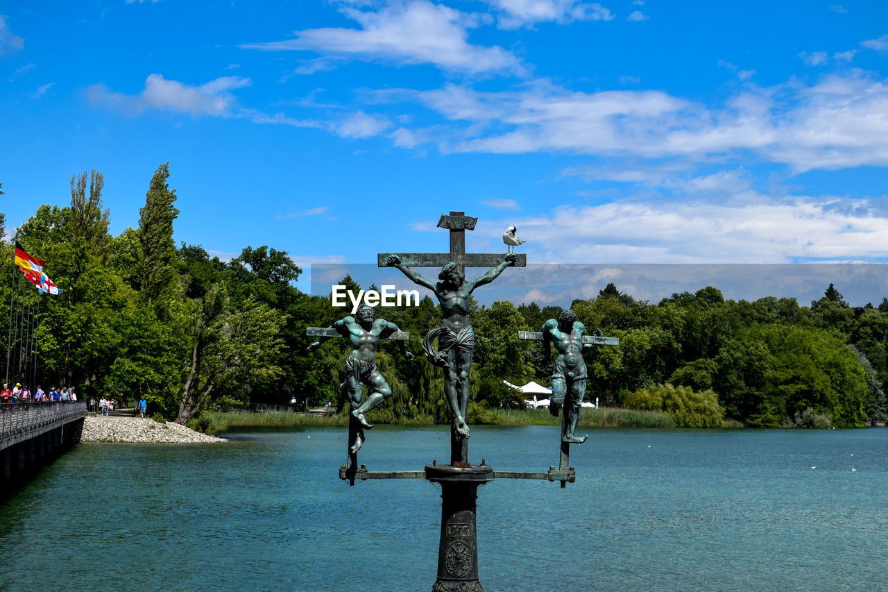 Statue by river against sky
