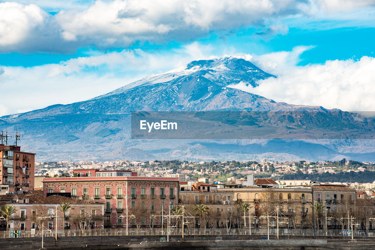 Scenic view of town by mountains against sky