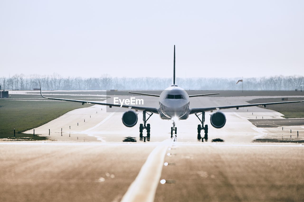 airplane, transportation, air vehicle, mode of transportation, sky, airport, airport runway, day, travel, clear sky, nature, runway, no people, public transportation, aircraft wing, outdoors, copy space, aerospace industry, sunlight, stationary, plane