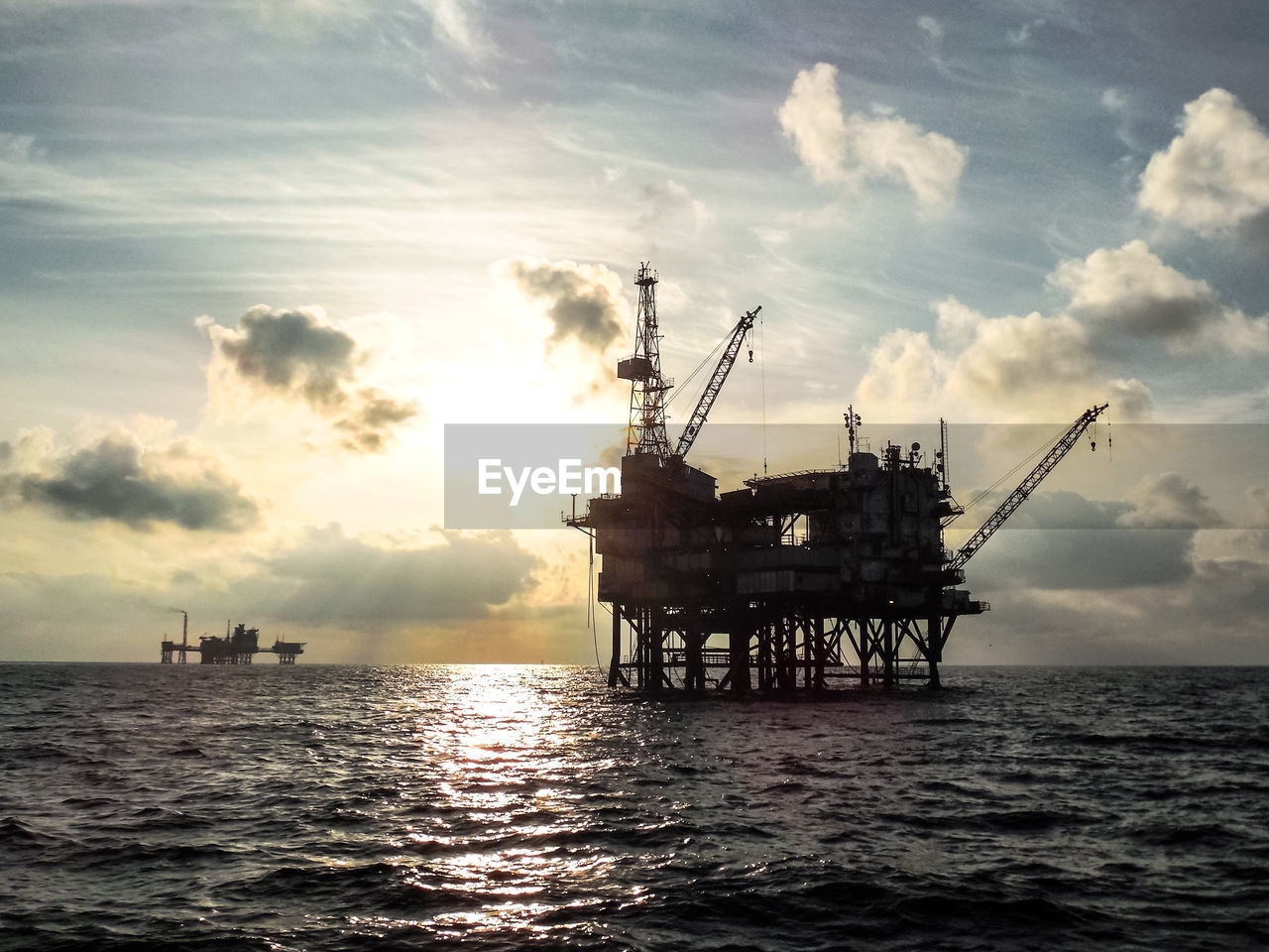 sky, water, offshore platform, sea, cloud - sky, industry, drilling rig, oil industry, fuel and power generation, built structure, waterfront, nature, sunset, no people, crude oil, crane - construction machinery, fossil fuel, gasoline, machinery, outdoors, horizon over water
