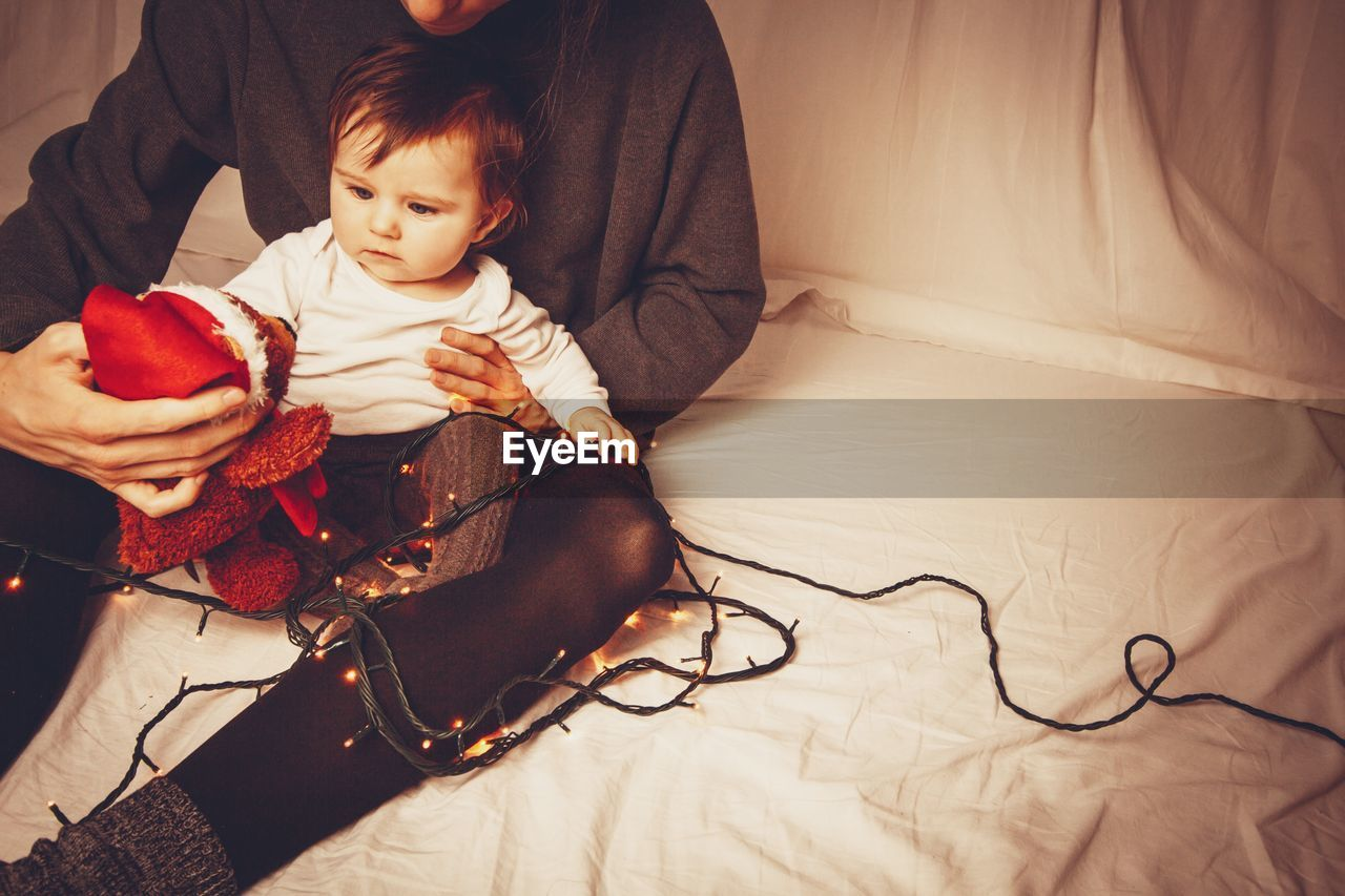 child, real people, indoors, front view, childhood, sitting, home interior, furniture, lifestyles, casual clothing, innocence, bed, people, cute, sofa, family, togetherness, women, men
