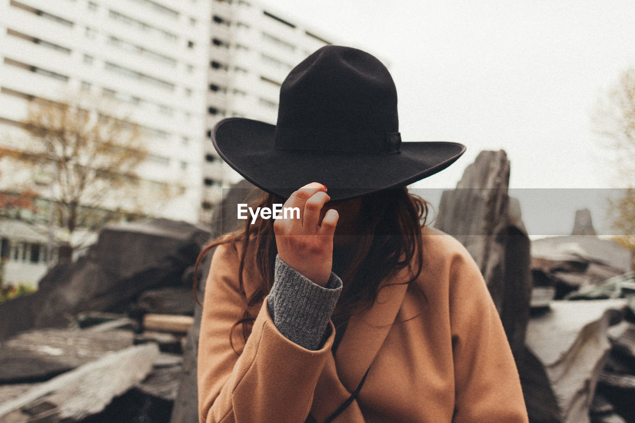 hat, clothing, one person, real people, lifestyles, architecture, focus on foreground, headshot, city, leisure activity, portrait, built structure, day, adult, front view, building exterior, standing, women, holding, obscured face, outdoors, hairstyle