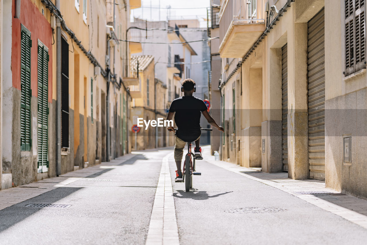 REAR VIEW OF PERSON RIDING BICYCLE ON STREET AMIDST BUILDINGS IN CITY