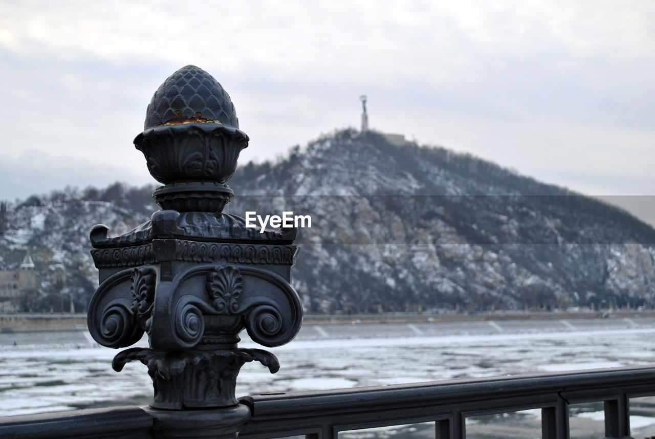 sky, nature, focus on foreground, day, water, winter, no people, railing, mountain, cold temperature, cloud - sky, sculpture, scenics - nature, representation, tranquil scene, tranquility, snow, outdoors