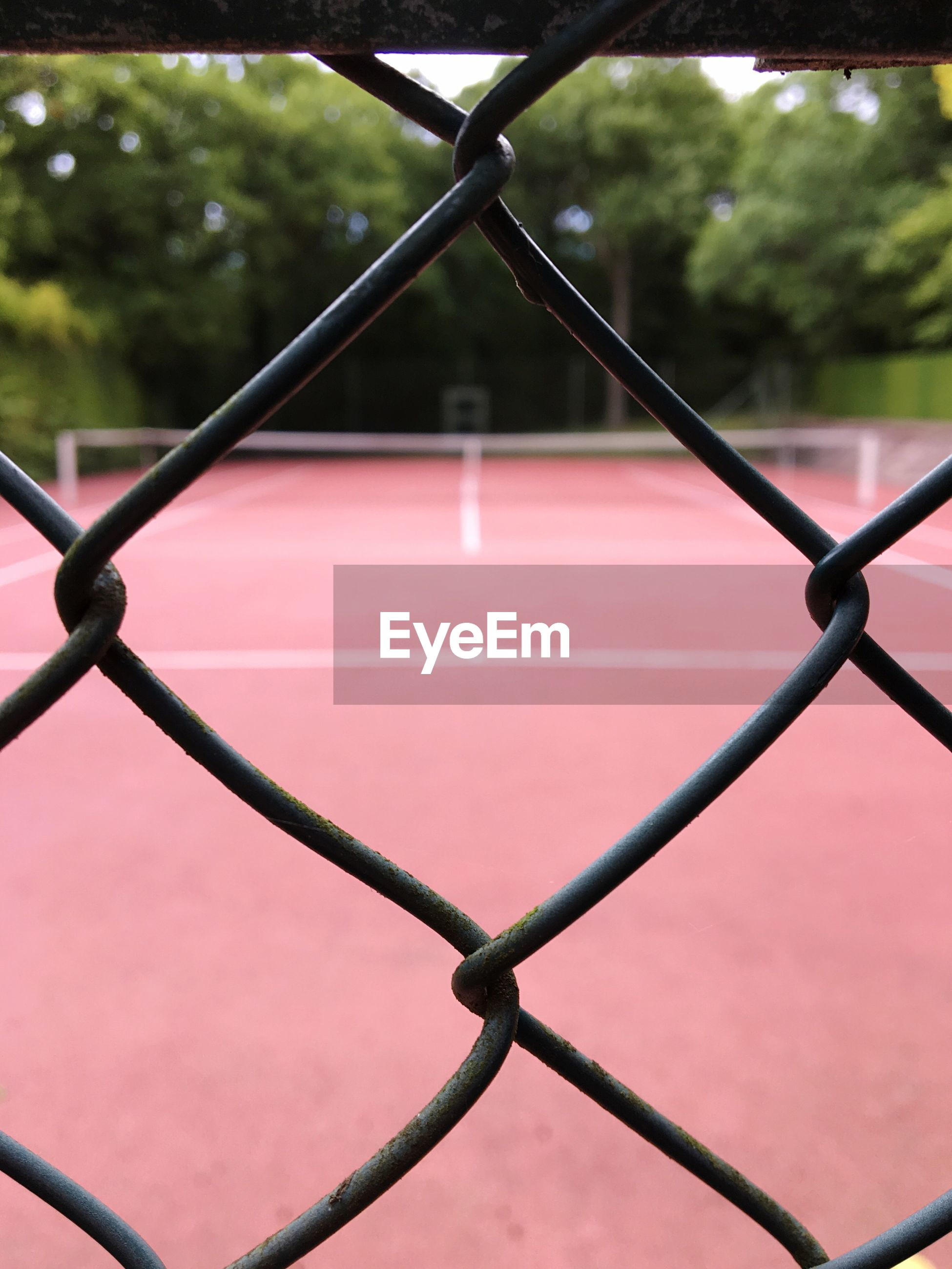 Tennis court seen through chainlink fence