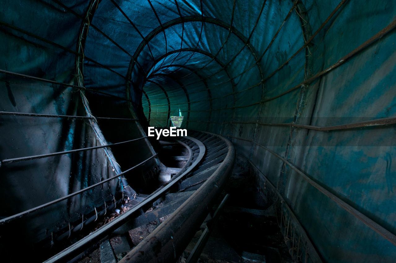 Railroad Tracks In Illuminated Tunnel