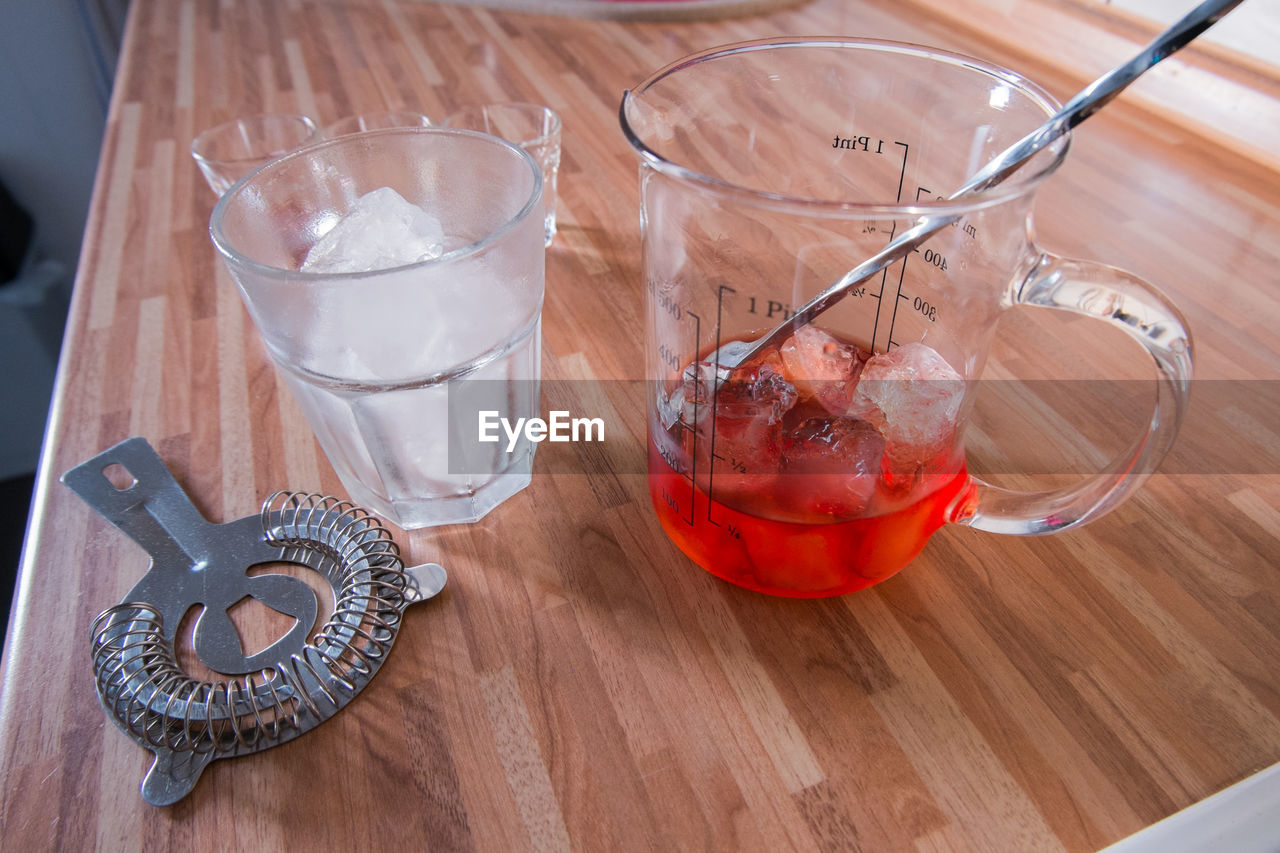 table, food and drink, high angle view, indoors, wood - material, transparent, glass, still life, refreshment, drink, freshness, no people, household equipment, glass - material, food, close-up, drinking glass, red, fruit