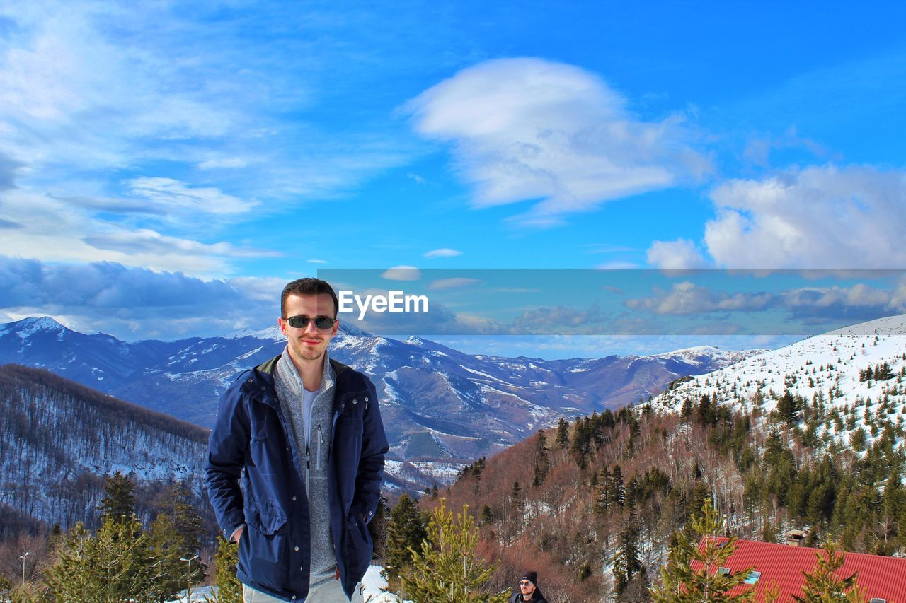 Portrait Of Man In Sunglasses Standing On Snowcapped Mountain