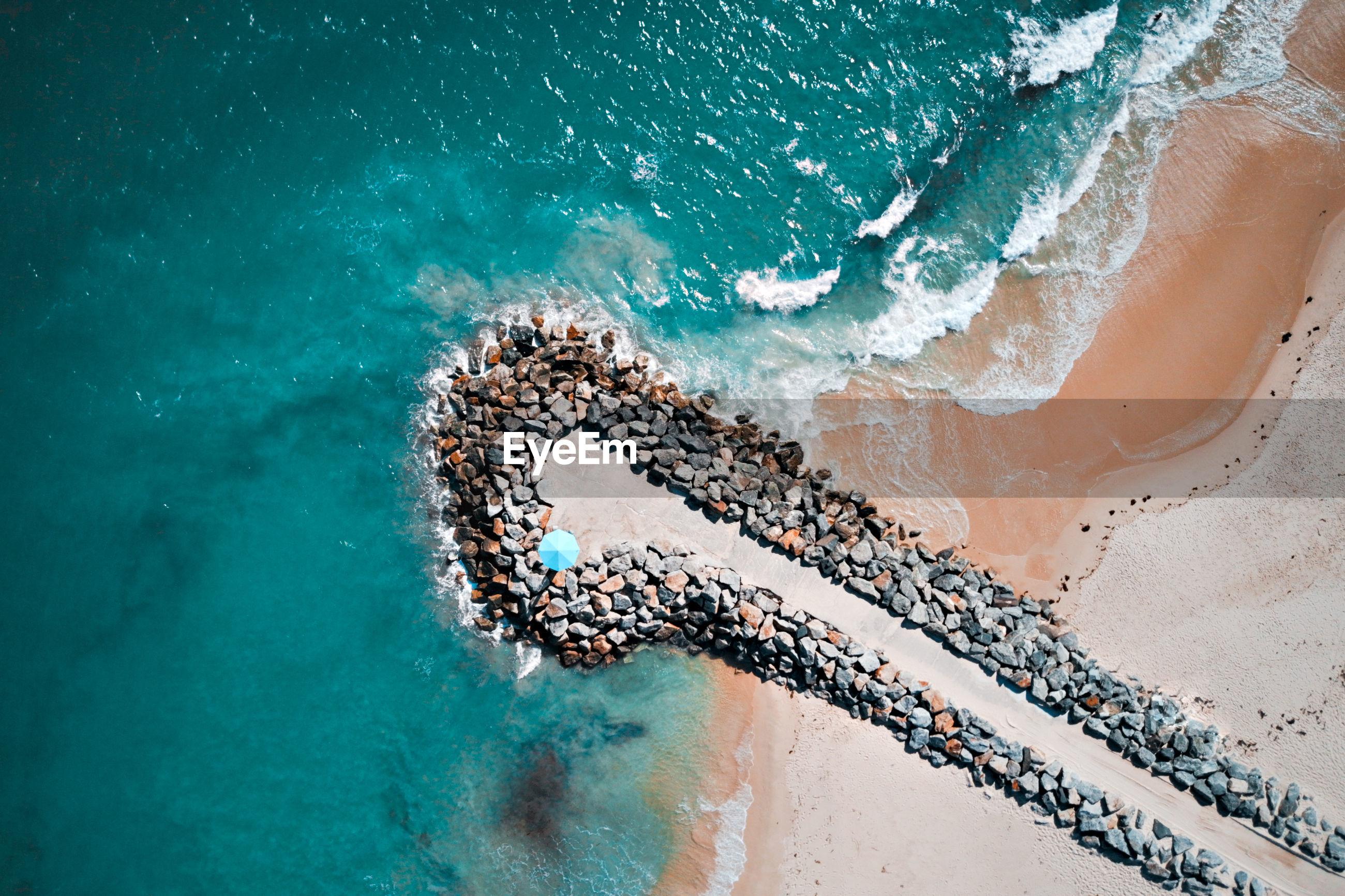 High angle view of sea waves on beach