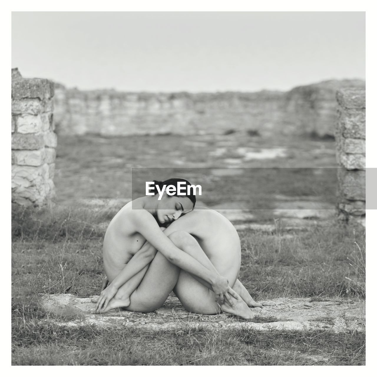 Side View Of Naked Women Embracing While Sitting On Field