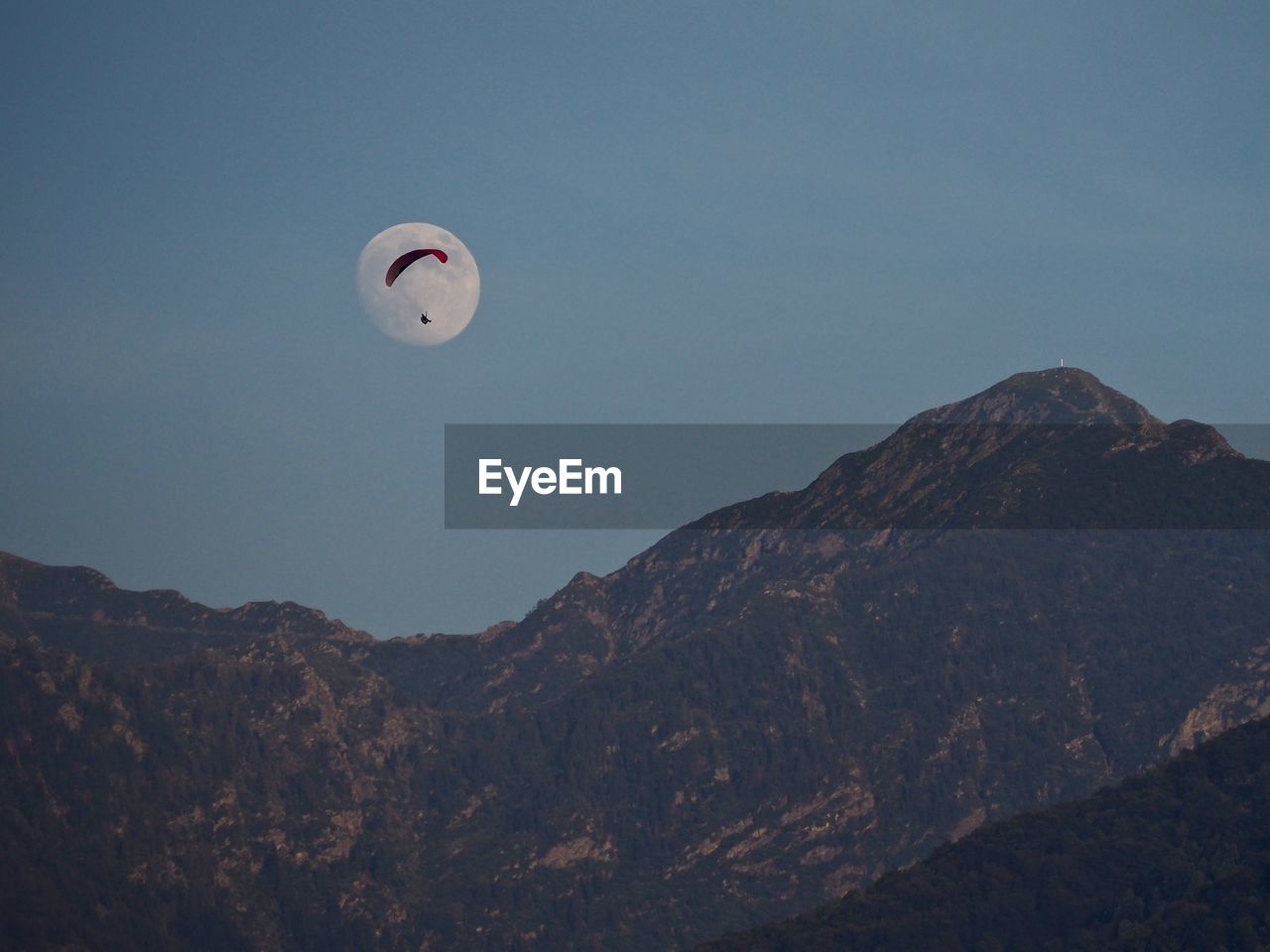 Low angle view of a paraglider in front of the moon in mountains against clear sky