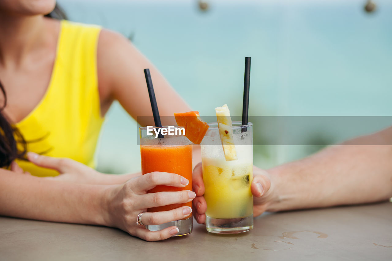 Midsection Of People Holding Drinks On Table