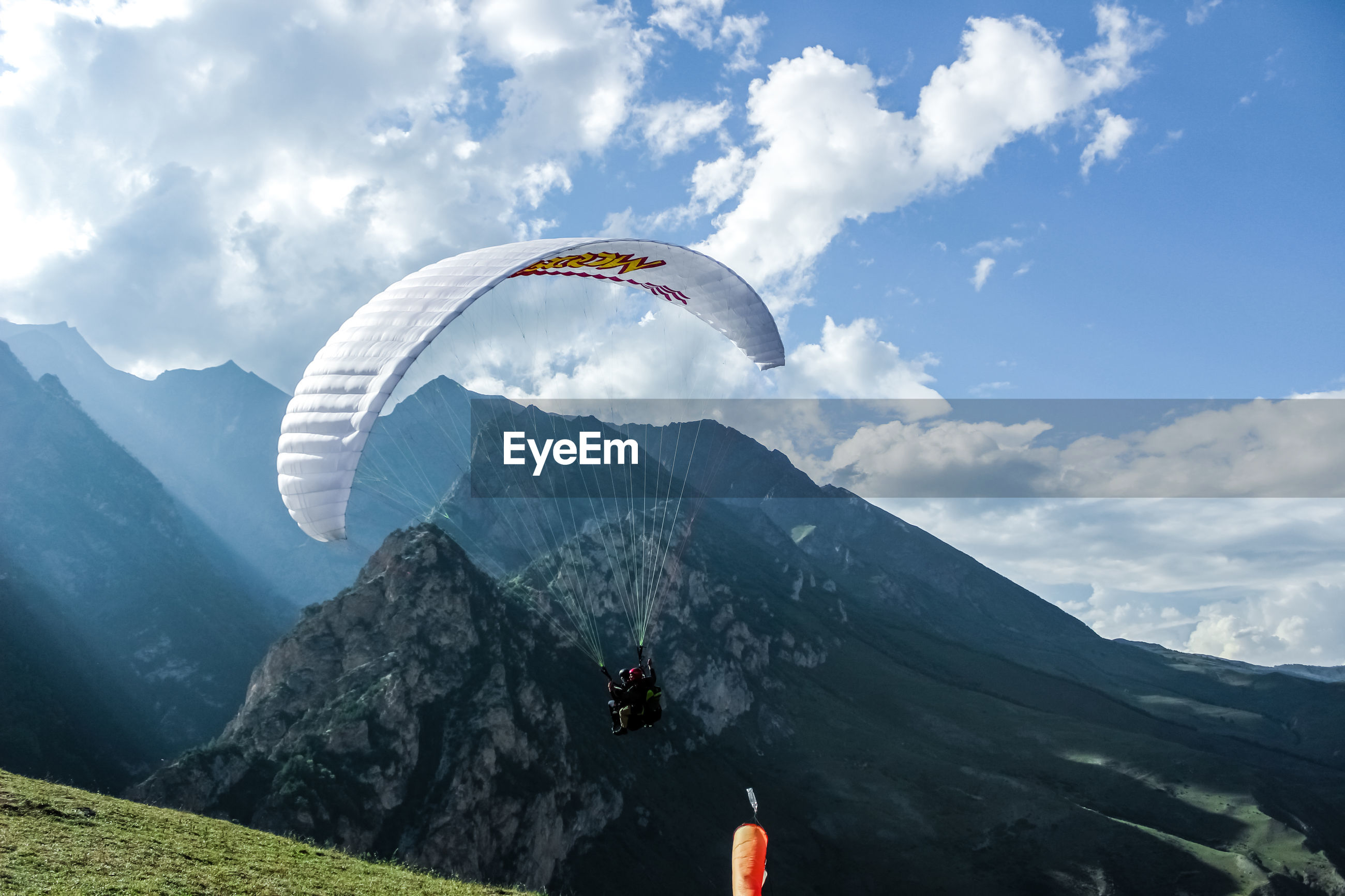 PEOPLE PARAGLIDING AGAINST MOUNTAINS