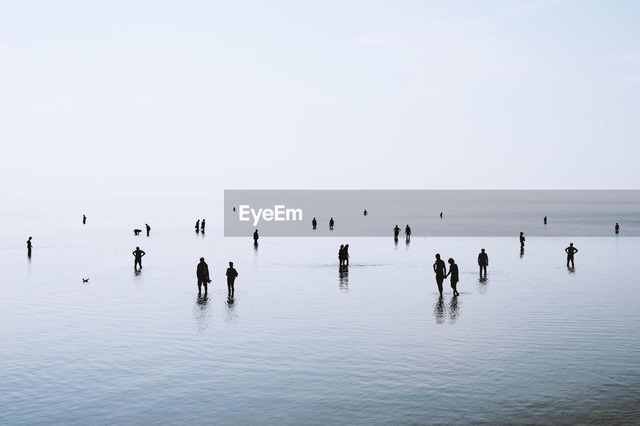 People in sea against clear sky
