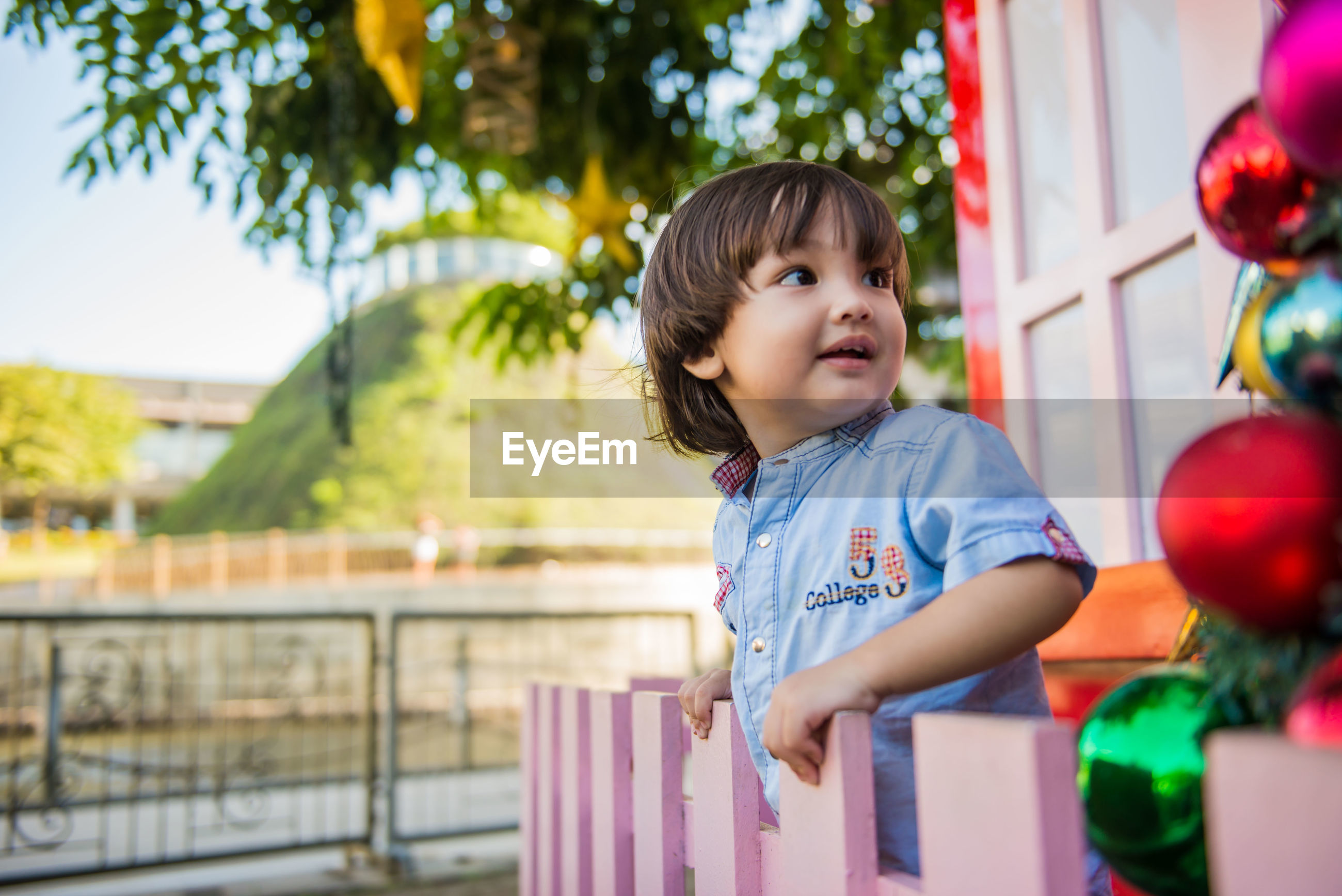 Boy looking away while standing against blurred background