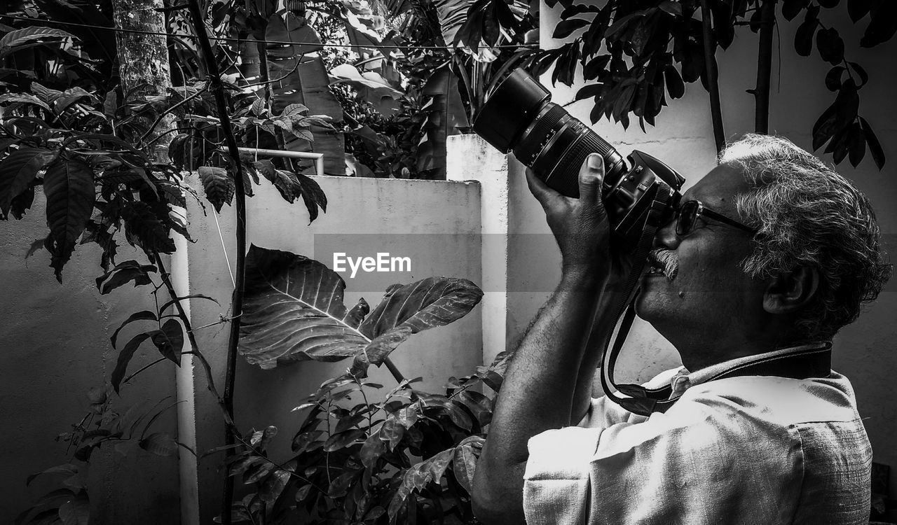 Side view of man photographing with camera while standing against plants