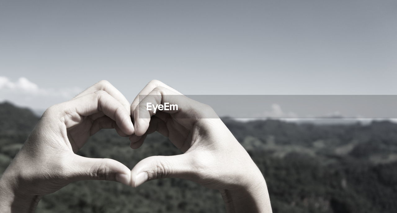 human hand, hand, human body part, one person, sky, focus on foreground, human finger, body part, real people, finger, heart shape, lifestyles, day, nature, close-up, unrecognizable person, leisure activity, copy space, personal perspective, positive emotion, human limb