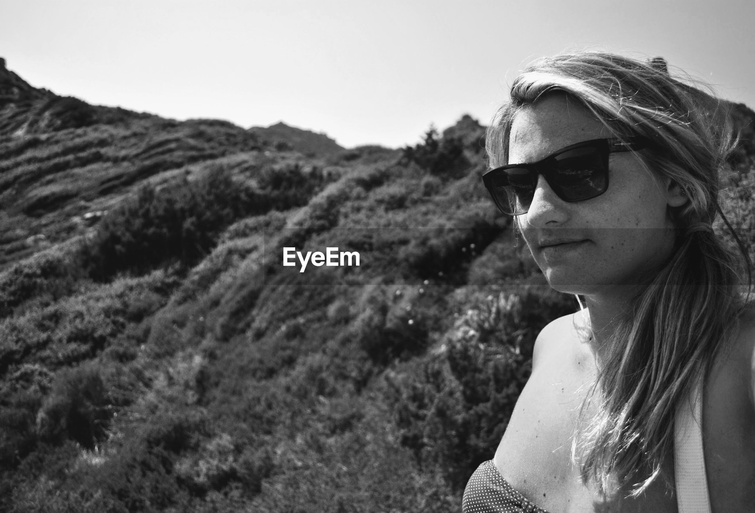 Young woman wearing sunglasses standing against hill
