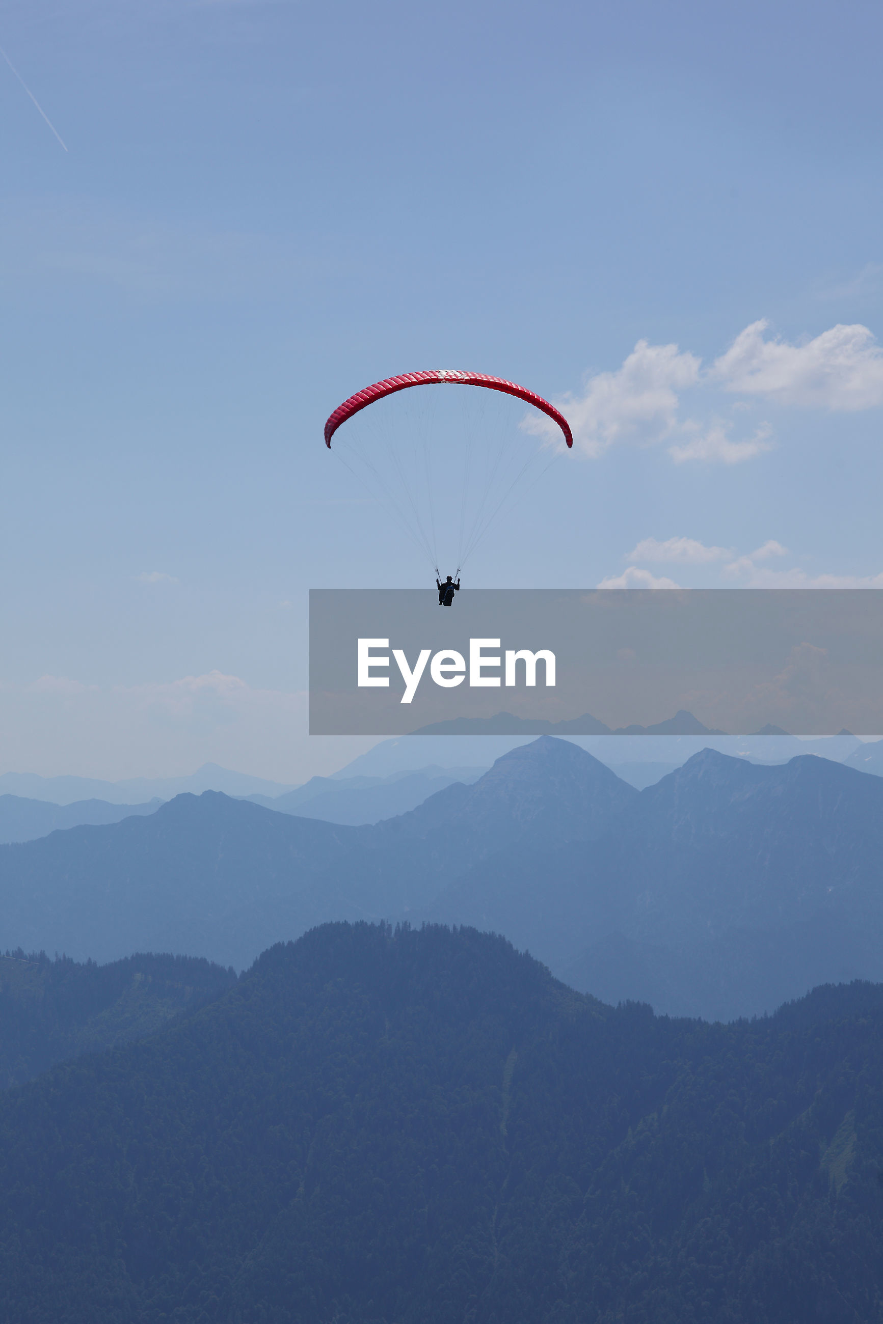 PERSON PARAGLIDING AGAINST MOUNTAIN RANGE