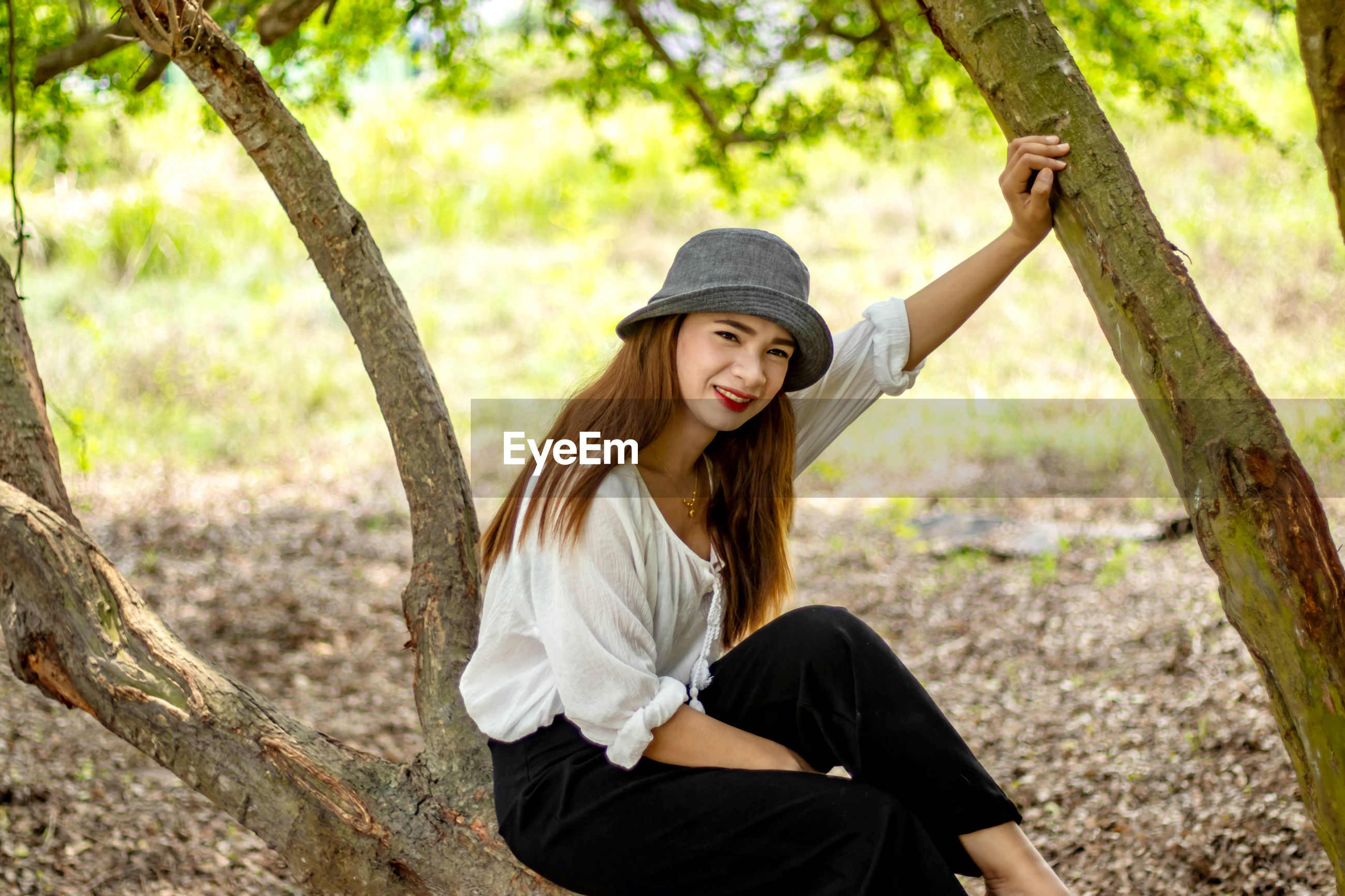 Portrait of smiling woman in hat sitting on tree