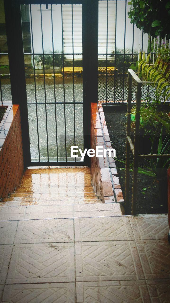 flooring, architecture, tile, day, no people, built structure, tiled floor, indoors, building, entrance, door, reflection, window, plant, wet, architectural column, glass - material, transparent, rain
