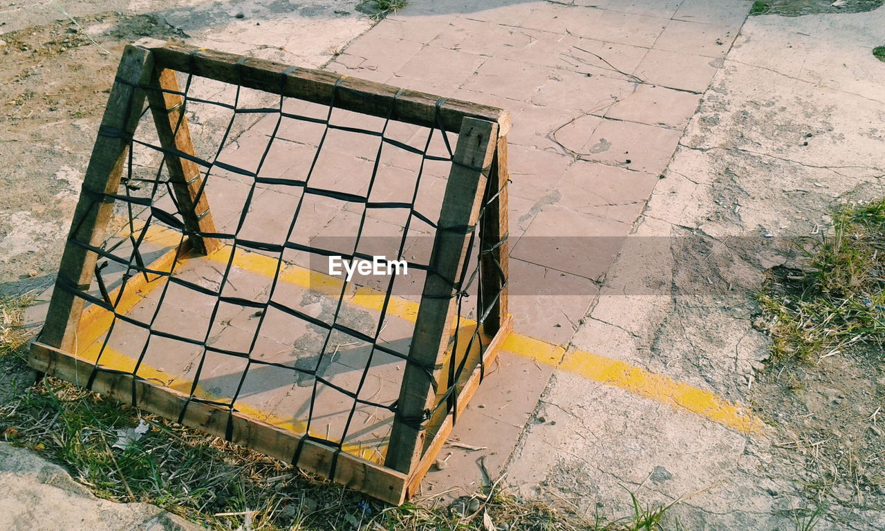 high angle view, day, no people, metal, nature, pattern, outdoors, sunlight, street, footpath, shadow, yellow, land, shape, grass, close-up, safety, design, field, security, tiled floor, concrete