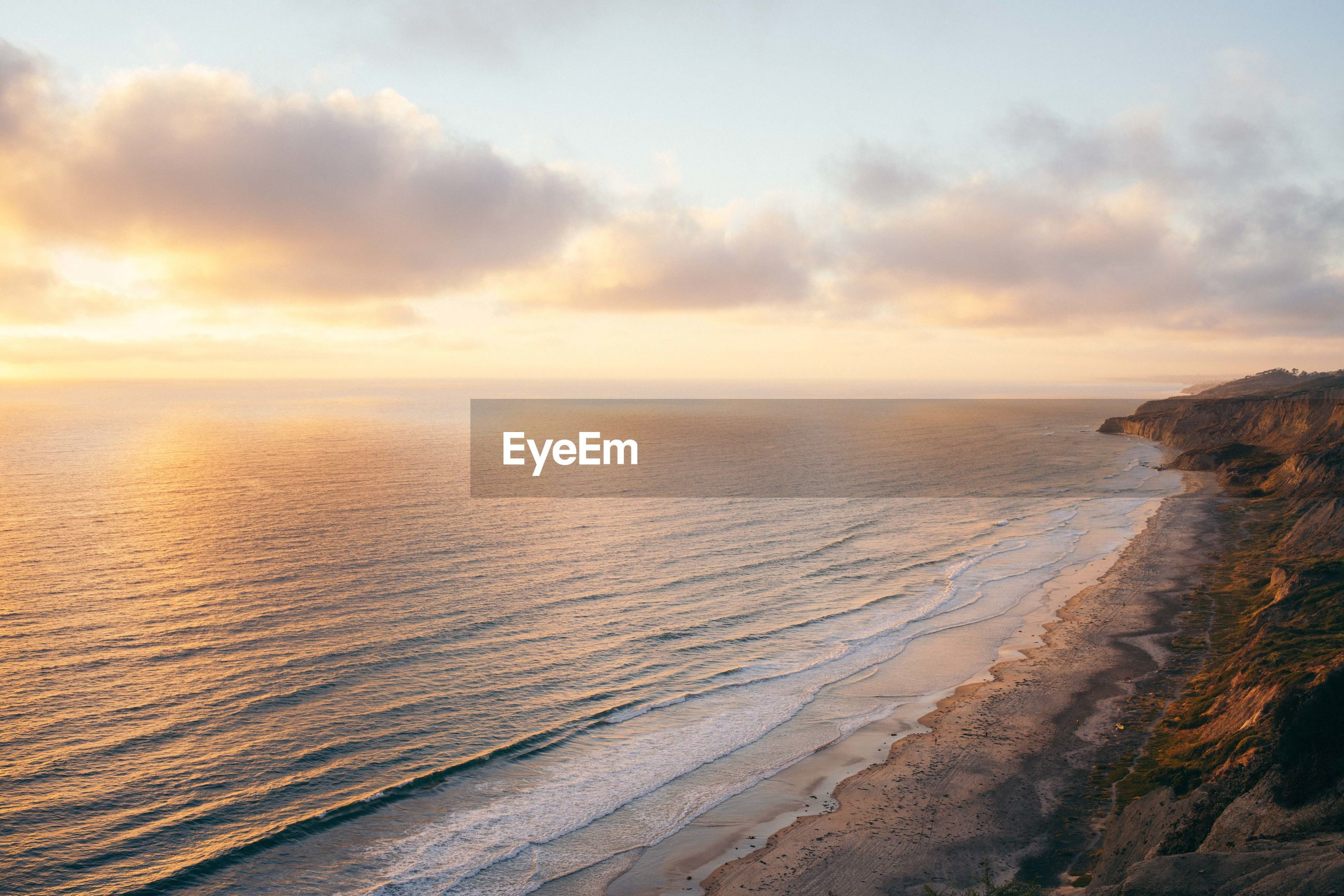 Scenic view of seascape against cloudy sky during sunset