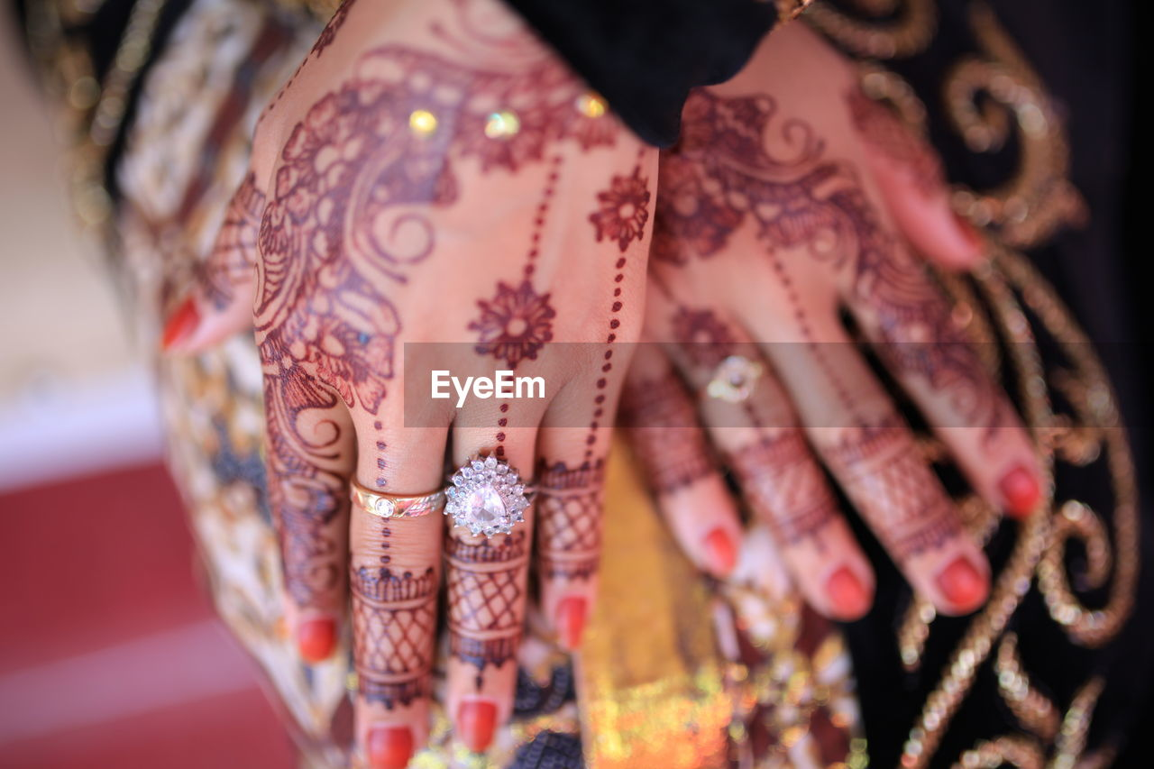 Midsection Of Woman Hands With Henna Tattoo And Diamond Ring