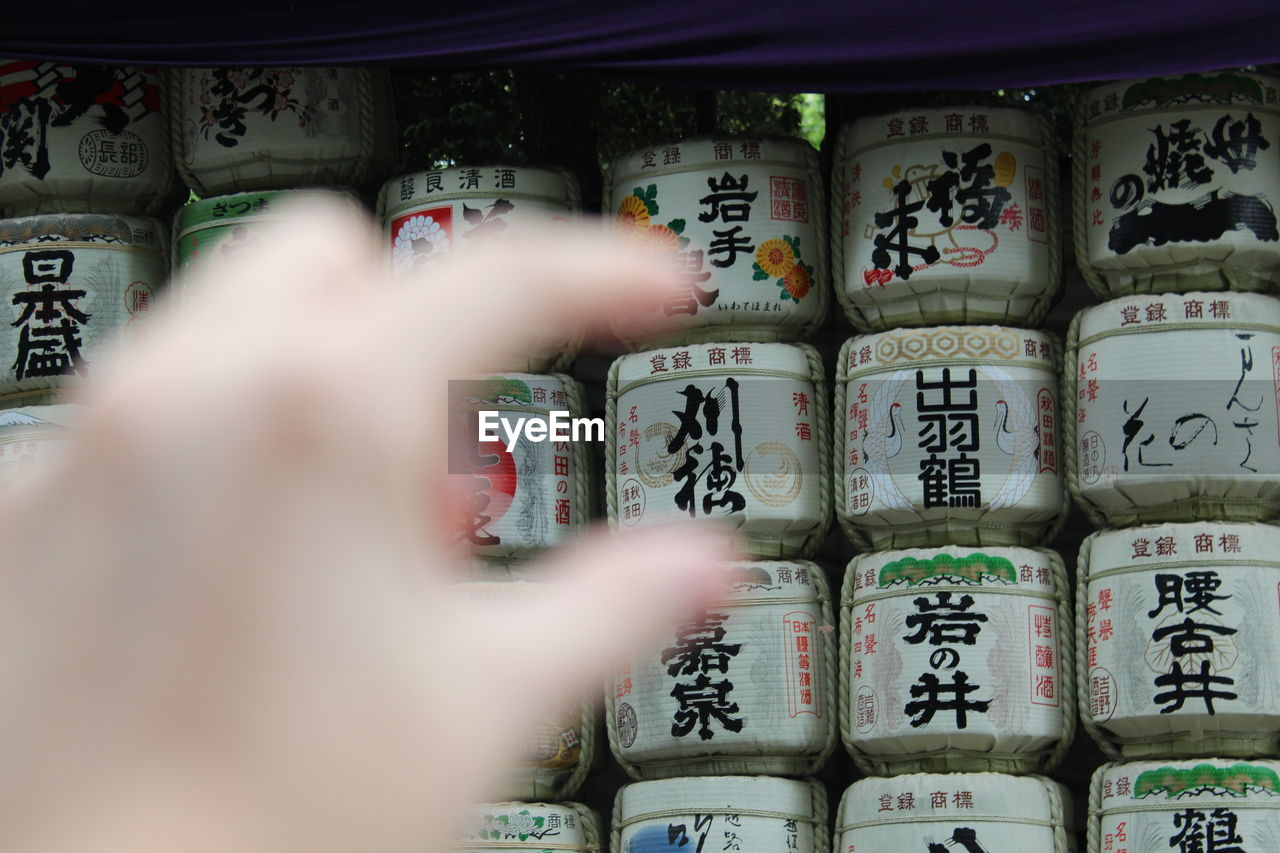 Close-Up Of Hand Gesturing Against Jars With Texts In Shelf