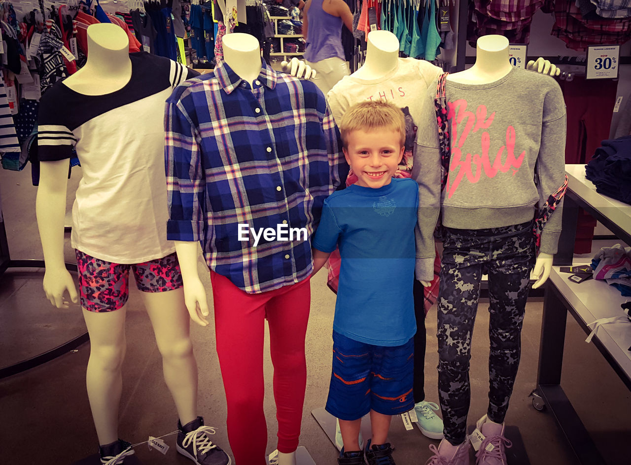 Portrait of happy boy standing by mannequins in store