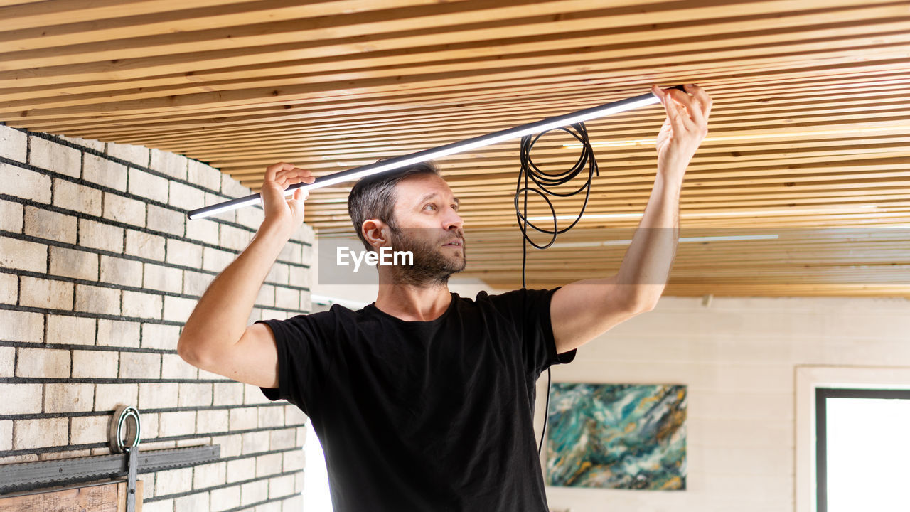 An electrician installs low voltage led lamps in a pine plank ceiling.  lamps raplacement service.