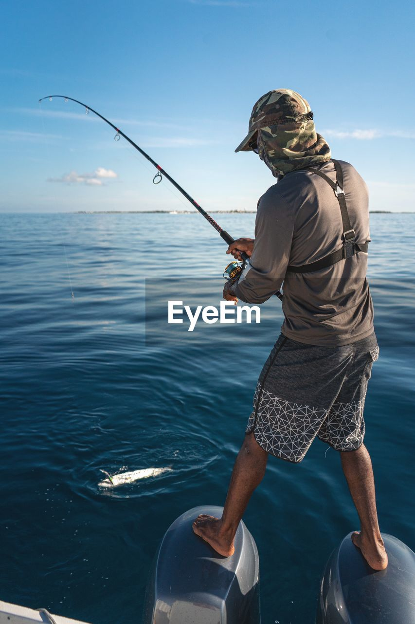 water, sea, fishing, one person, rod, leisure activity, fishing rod, real people, holding, lifestyles, nature, sky, activity, men, sport, beauty in nature, horizon over water, scenics - nature, outdoors