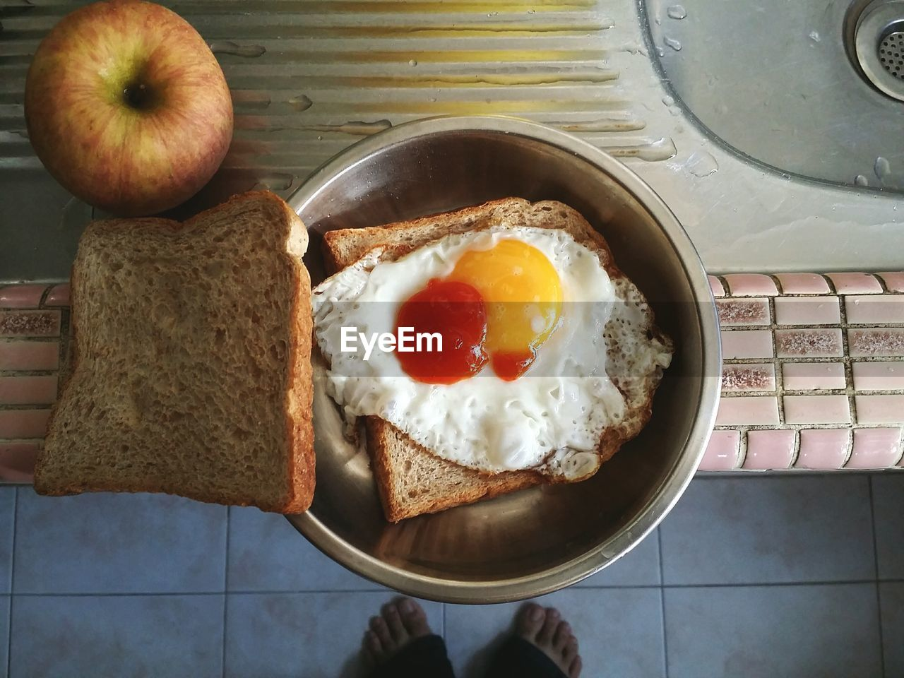 Low Section Of Person Standing By Fried Egg With Breads In Kitchen