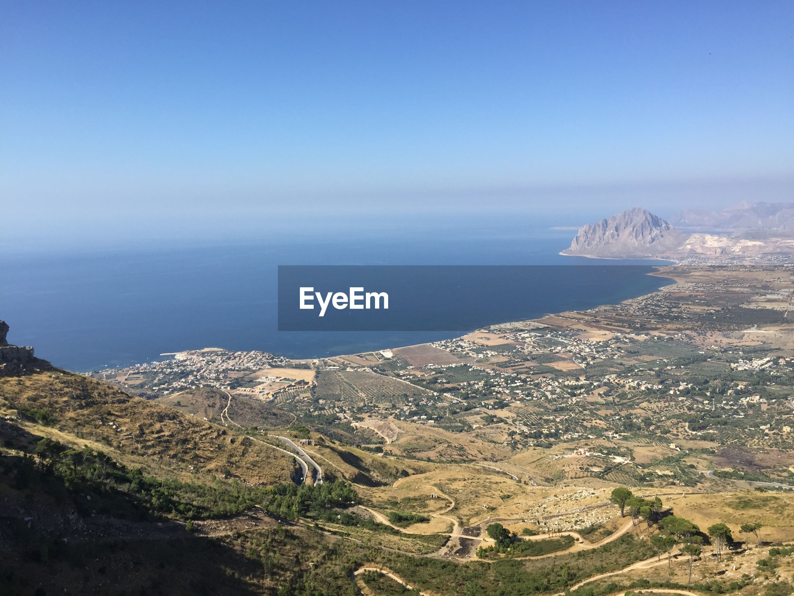HIGH ANGLE VIEW OF SEA AND LANDSCAPE AGAINST CLEAR SKY