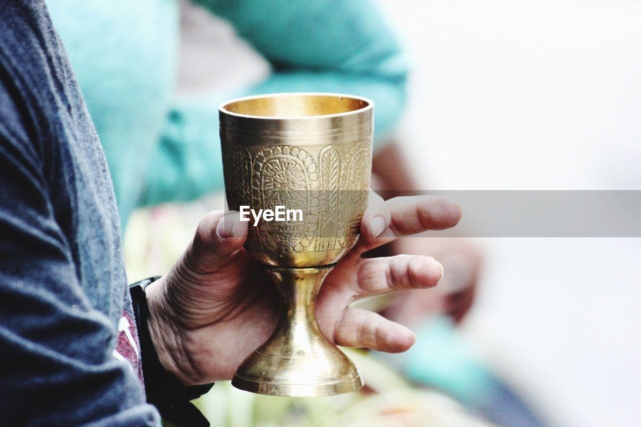 Close-Up Of Hand Holding Golden Goblet