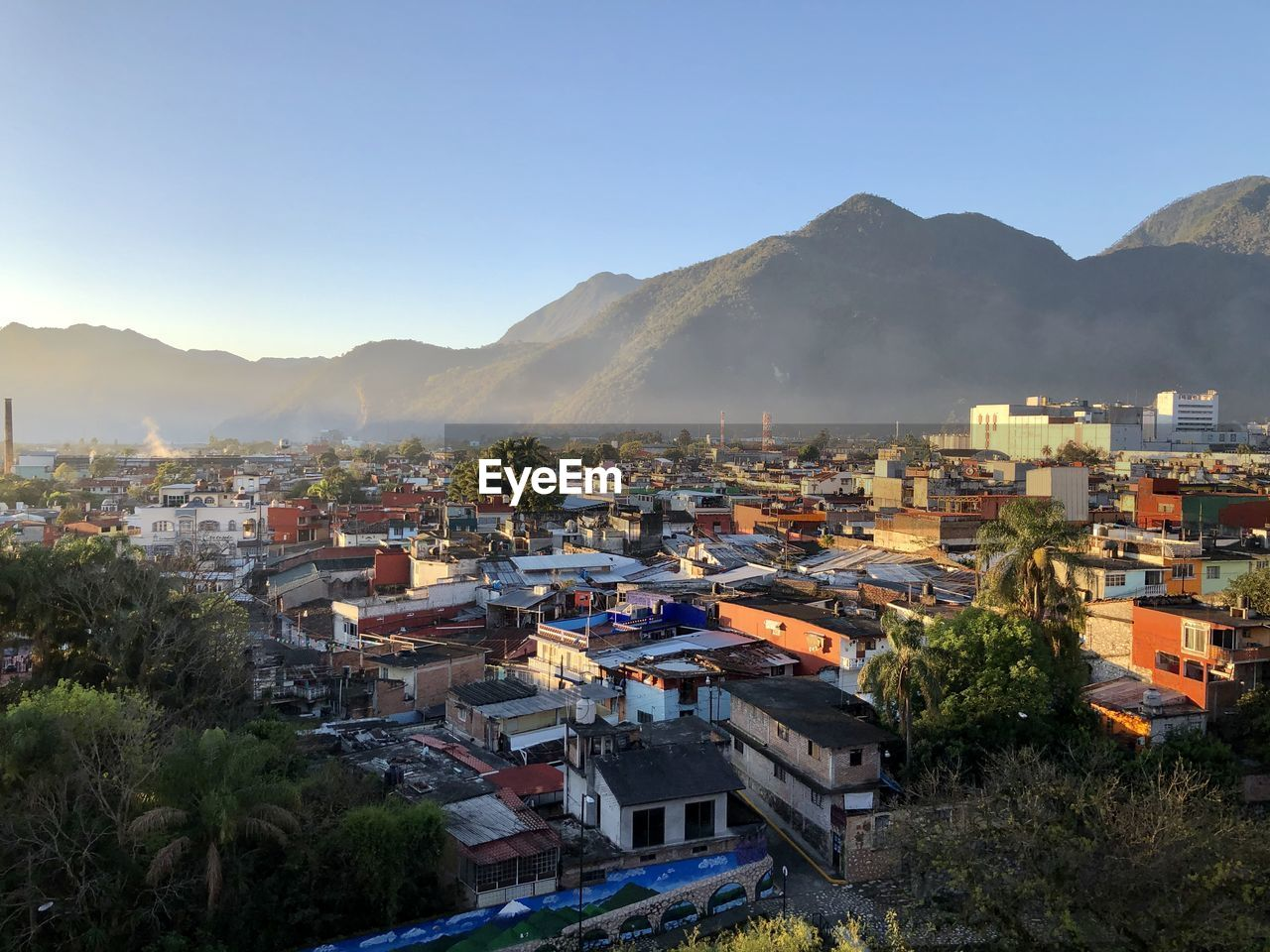 High angle view of townscape and mountains against clear sky