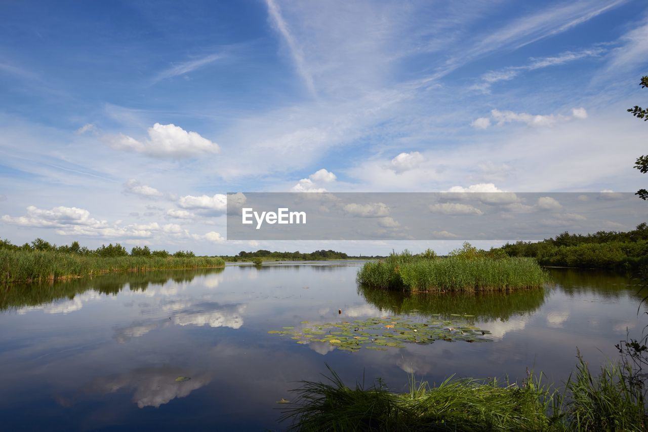 Scenic View Of River Amidst Grassy Field Against Cloudy Sky