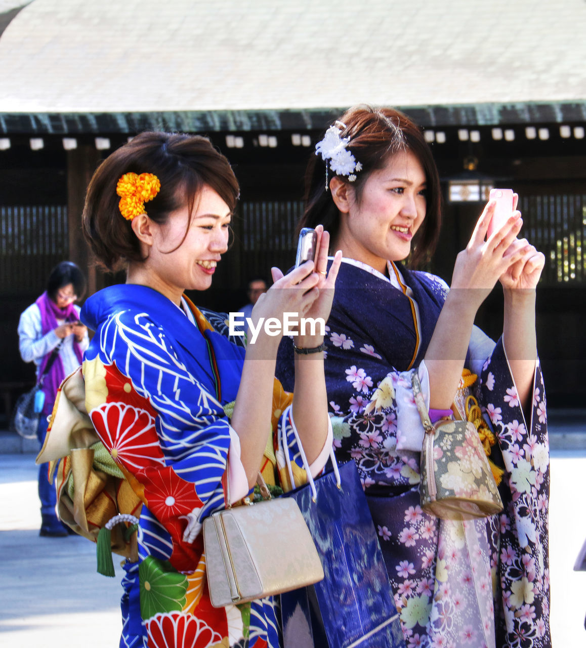 real people, cultures, young women, traditional clothing, young adult, lifestyles, outdoors, women, kimono, religion, holding, leisure activity, beautiful woman, togetherness, day, architecture, portrait, adult, people