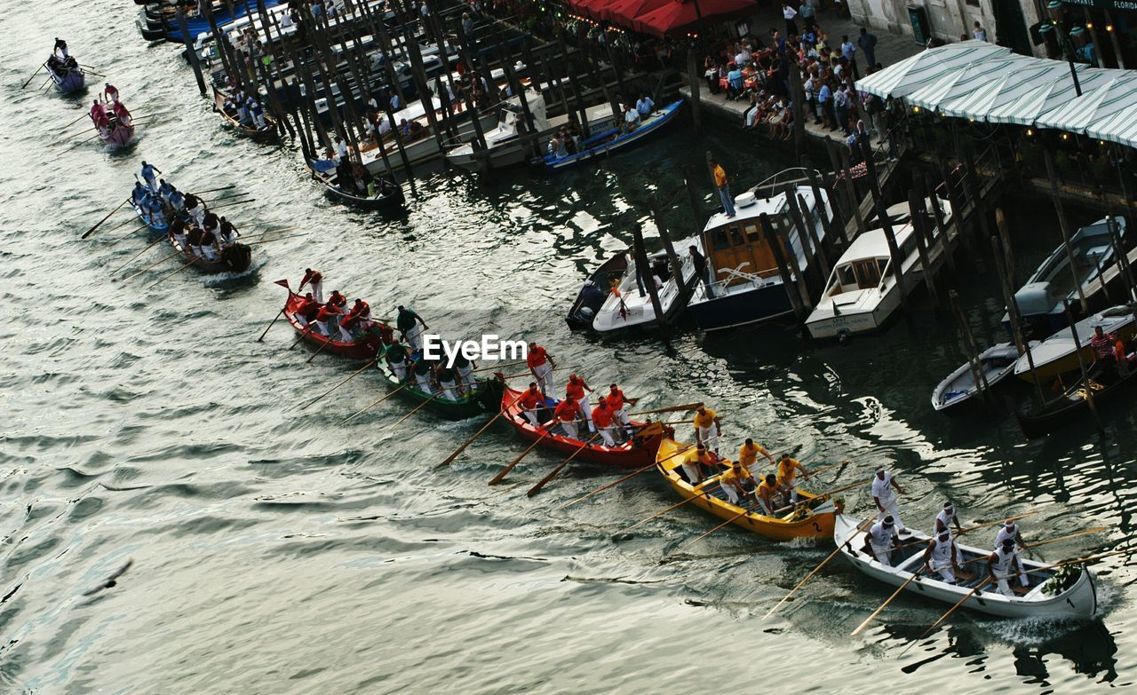large group of people, nautical vessel, real people, transportation, high angle view, river, mode of transport, water, men, day, rowing, leisure activity, outdoors, women, rowboat, lifestyles, competition, sport, rafting, teamwork, sport rowing, sculling, adult, people, adults only