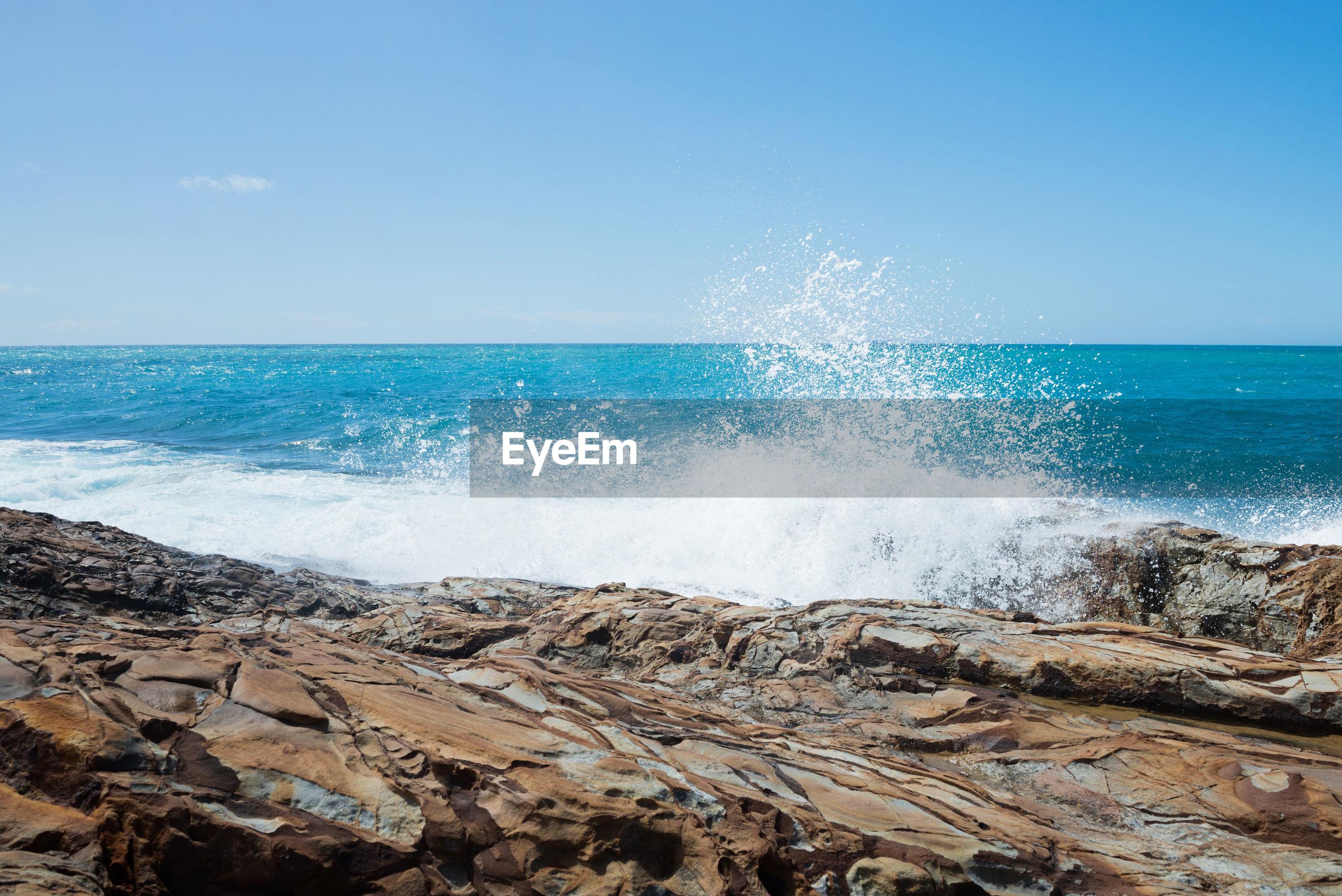 Waves splashing on rocks at shore against blue sky