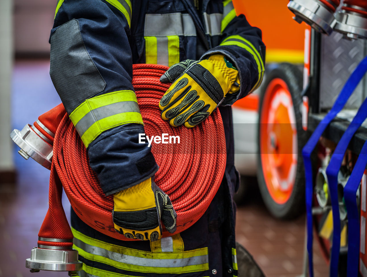 Midsection of firefighter holding hose at fire station