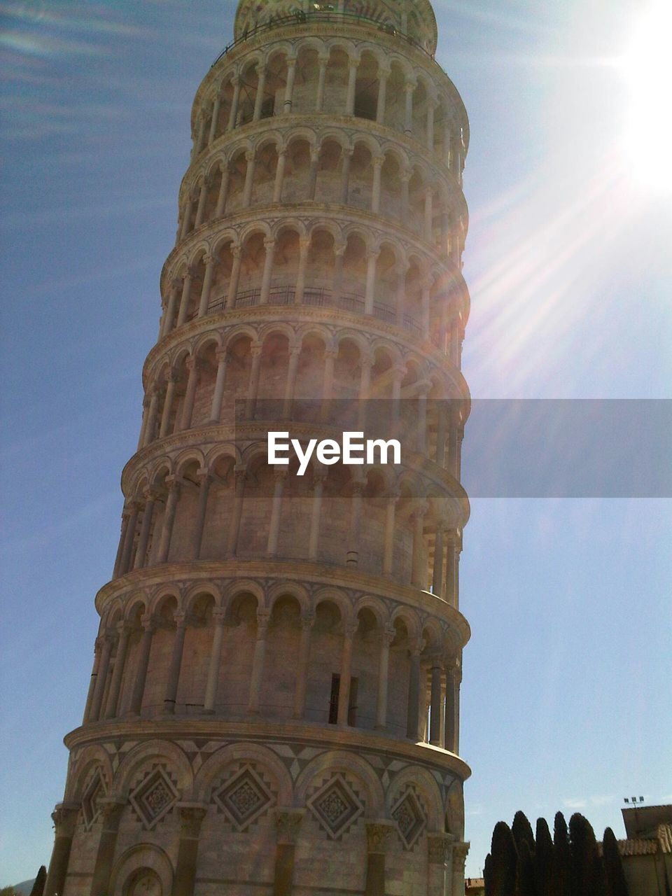 Low angle view of leaning tower of pisa against bright sky