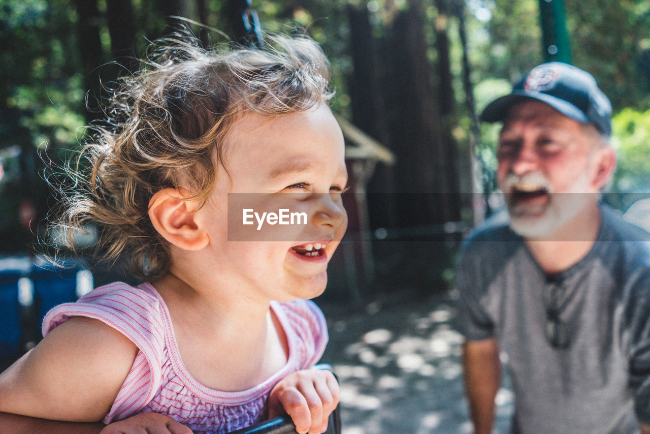 Cheerful granddaughter playing at playground by grandfather