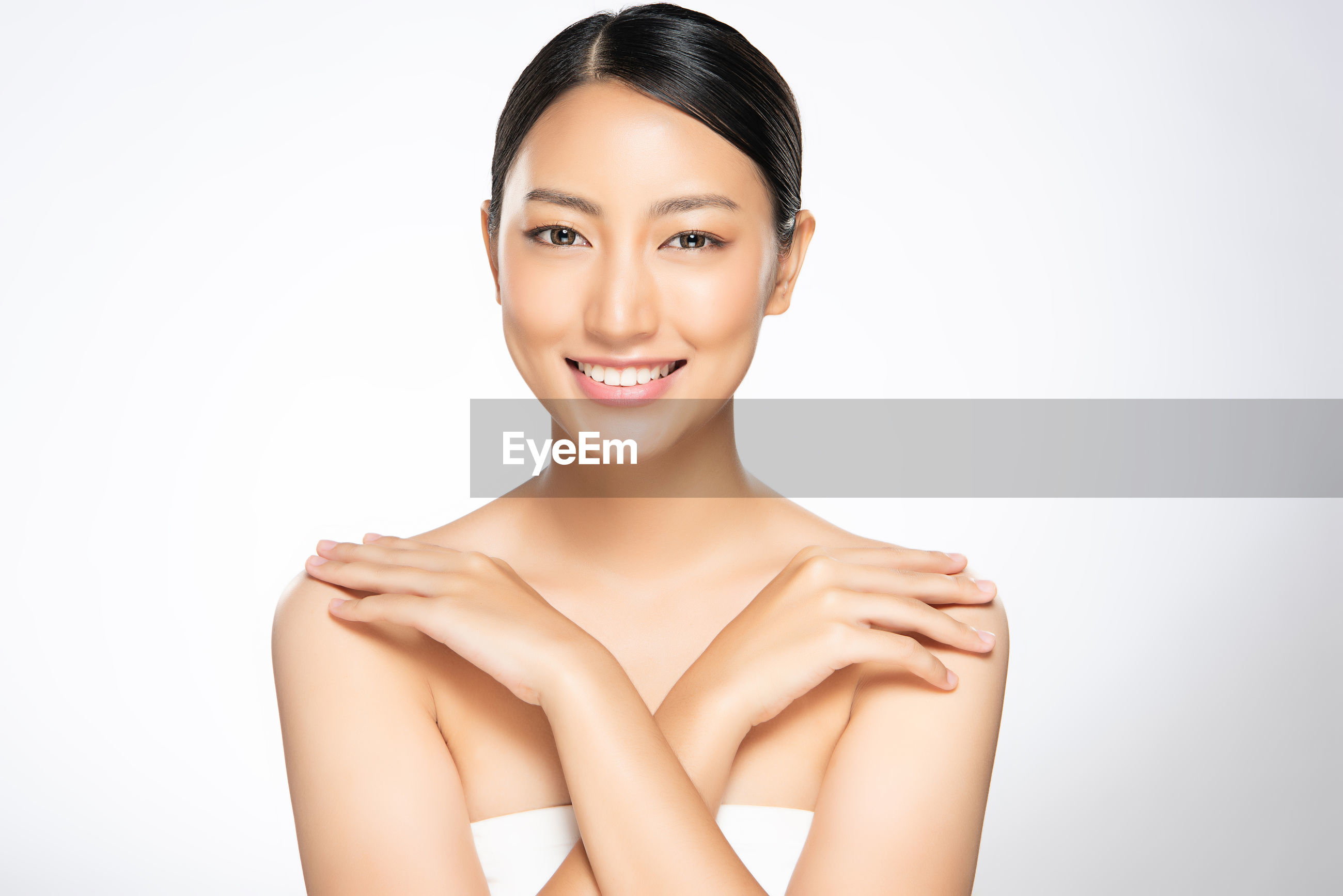 Portrait of smiling beautiful woman against white background