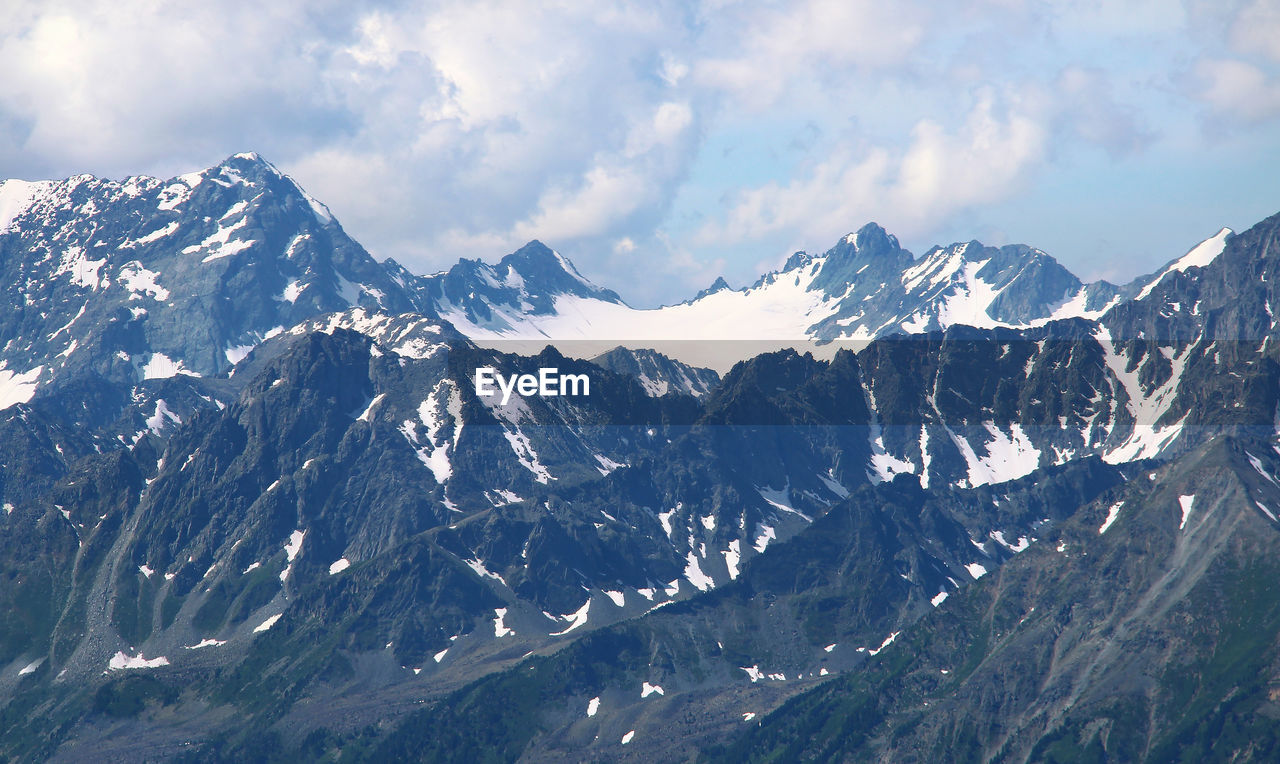 Alpine snow-capped ridges and peaks in the form of a bowl against a sky with clouds